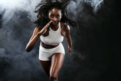Sprinter noir sportif fort de femme de peau, courant sur le fond avec de la fumée portant dans les vêtements de sport figure que  photos libres de droits