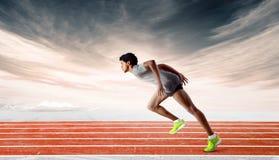 Sprinter på spåret som framåtriktat lutar Arkivbild