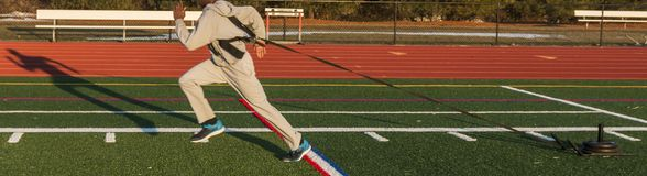 Sprinter pulling a weighted sled. A high school track and field sprinter is pulling a weighted sled across a green turf field with his full shadow in view late Stock Photos