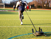 Sprinter pulling a weighted sled. Track and field sprinter pulling a weighted sled on a green turf field during sprinting practice stock image