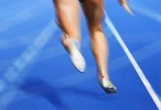 Sprinter race track blur. Legs of female runner blurred on blue race track Royalty Free Stock Image