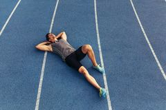 Sprinter relaxing by lying on the running track. Runner lying on the track in a relaxed mood with hands under his head. Athlete relaxing after a run Royalty Free Stock Photography