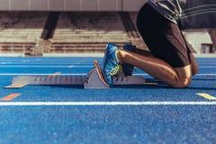 Sprinter reposant ses pieds sur le bloc commençant sur la voie courante Photo stock