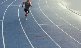 Sprinter running on track. Athlete running on an all-weather running track alone. Runner sprinting on a blue rubberized running track Stock Image