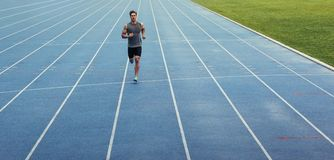 Sprinter running on track. Athlete running on an all-weather running track alone. Runner sprinting on a blue rubberized running track Stock Photos