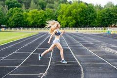 The sprinter runs on stadium. The sportswoman prepares for competitions Stock Photos