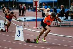 Sprinter som lämnar startgrop på det rinnande spåret Royaltyfria Foton