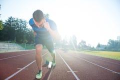 Sprinter som lämnar startgrop på det rinnande spåret explosiv start royaltyfri foto