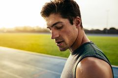 Sprinter standing on running track. Closeup of a sprinter standing on a running track. Runner looking down standing on the track with sweat dripping from face Stock Image