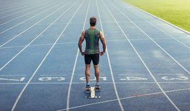Sprinter standing on starting block on running track. Rear view of an athlete ready to sprint on an all-weather running track. Runner using a starting block to Stock Photo
