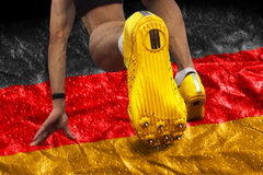 Sprinter start position german flag. Sprinter starts on banner with german national colors Royalty Free Stock Photography