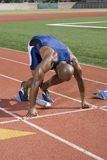 Sprinter At Starting Block. African American male athlete in starting position on running track Royalty Free Stock Photos