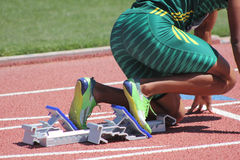 Sprinter in starting blocks. A sprinter in green tights prepares for his race in the starting blocks on the track. Taken at an invitational track meet in Arizona Royalty Free Stock Images