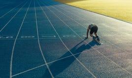 Sprinter sui suoi segni su una pista corrente Fotografia Stock