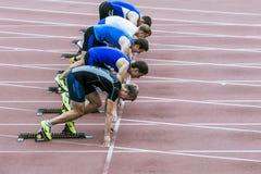 Sprinter sulla linea di inizio 100 m. Immagine Stock