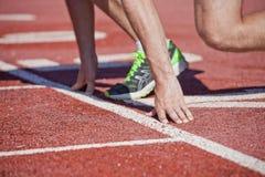 Sprinter sur la ligne de début du chemin courant de stade en caoutchouc Photo stock