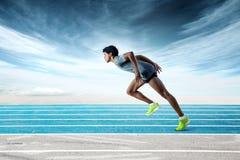 Sprinter sur la voie se penchant en avant Image stock