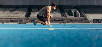 Sprinter sur ses marques sur une voie courante Images stock