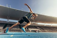 Free Sprinter Taking Off From Starting Block On Running Track Stock Images - 102578064