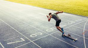 Sprinter taking off from starting block on running track. Rear view of an athlete starting his sprint on an all-weather running track. Runner using starting Stock Images