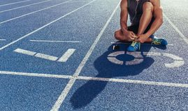Sprinter tying shoe lace sitting on running track Royalty Free Stock Images