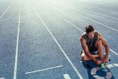 Sprinter tying shoe lace sitting on running track. Athlete sitting on a running track tying shoe lace while listening to music. Runner wearing earphones sitting Stock Image