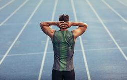 Sprinter warming up before a race. Rear view of an athlete standing on a running track with hands at the back of head. Runner getting ready to race standing on Stock Images