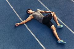 Sprinter warming up on the track. Athlete doing stretching exercises on the running track. Runner stretching muscles by lying on the track Stock Photo