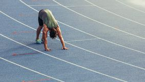 Sprinter warming up on the track. Athlete doing stretching exercises on the running track. Runner stretching muscles by touching the hands on the track Stock Images