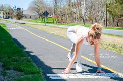 Sprinter woman getting ready to start on the running track. Female runner is waiting for the start signal Stock Photos