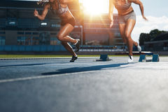 Sprinters starts out of the blocks. On athletics racetrack with bright sunlight. Low section shot of female athletes starting a race in stadium with sunflare Stock Photography