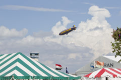 Spririt of GoodYear Blimp flying over tents Royalty Free Stock Image