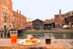 Spritz Aperol drink with venetian traditional snacks cicchetti on the water chanal background in Venice. stock photography