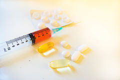 Spritze, die rotes flüssiges Blut neben Pillen und Blase enthält Stockfotografie