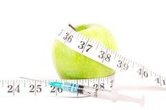 Spritze mit Apfel und messendem Band Lizenzfreie Stockbilder