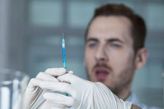Spritze mit der Droge in den Doktor ` s Händen Stockbilder