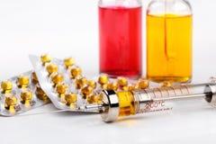 Spritze mit Medikation, Blisterpackung mit Pillen und Flaschen mit farbiger Flüssigkeit auf weißem Hintergrund Stockfotografie