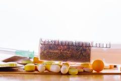 Spritze mit medizinischen Kräutern und Tabletten auf dem Tisch Lizenzfreie Stockfotografie