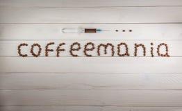 Spritze und Aufschrift Coffeemania-Kaffee gemacht von der Kaffeebohne Lizenzfreies Stockfoto