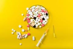 Spritze und bunte Pille und Kapseln auf Hintergrund Lizenzfreies Stockbild