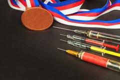 Spritze und Medaillen Lackierung im Sport Missbrauch von anabolen Steroiden für Sport Anabole Steroide verschüttet auf einem Holz Lizenzfreie Stockbilder