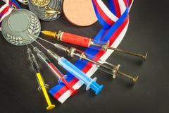 Spritze und Medaillen Lackierung im Sport Missbrauch von anabolen Steroiden für Sport Anabole Steroide verschüttet auf einem Holz Lizenzfreies Stockbild