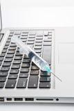 Spritzen auf einem Laptop Stockbilder