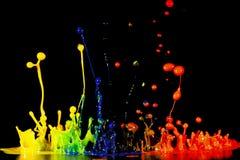 Spritzen der Acrylfarbe, abstrakter Hintergrund auf Schwarzem Lizenzfreies Stockfoto