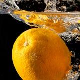 Spritzen der Orange auf Wasser Lizenzfreie Stockfotografie