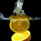 Spritzen der Orange auf Wasser Lizenzfreies Stockfoto
