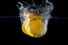 Spritzen der Orange auf Wasser Lizenzfreie Stockbilder