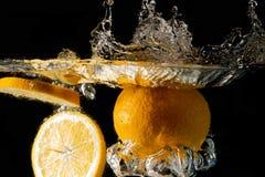 Spritzen der Orange auf Wasser Stockfotos