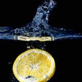 Spritzen der Orange auf Wasser Lizenzfreie Stockfotos