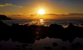 Spritzen der Welle über Felsen im Sonnenaufgang Lizenzfreies Stockfoto